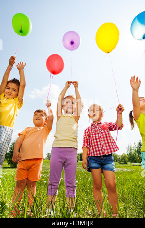 Funny kids with balloons in the air - Stock Photo