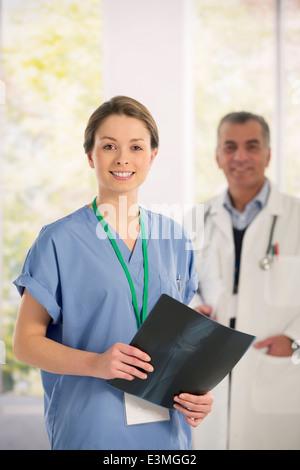 Portrait of confident nurse with x-ray - Stock Photo