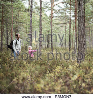 Girl showing something to father in forest - Stock Photo