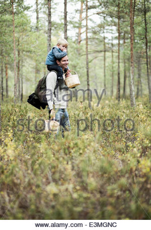 Father carrying son on shoulders in forest - Stock Photo