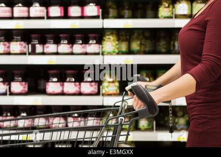 Cropped image of woman with shopping cart in supermarket - Stock Photo