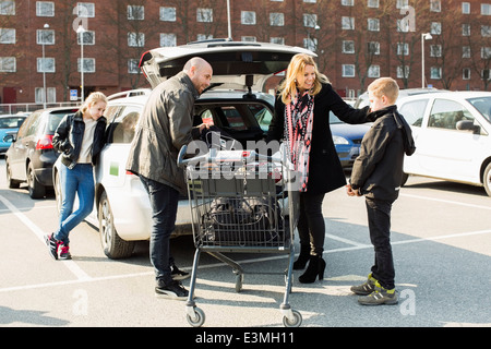 Family loading groceries in car trunk at parking lot - Stock Photo