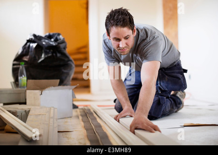 Male carpenter examining wooden plank at site - Stock Photo