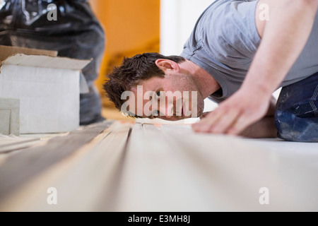 Male carpenter checking wooden plank at site - Stock Photo