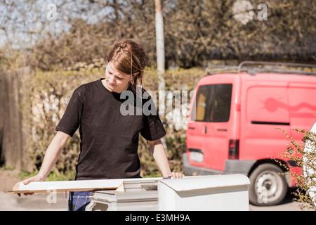 Female carpenter examining wooden plank outdoors - Stock Photo