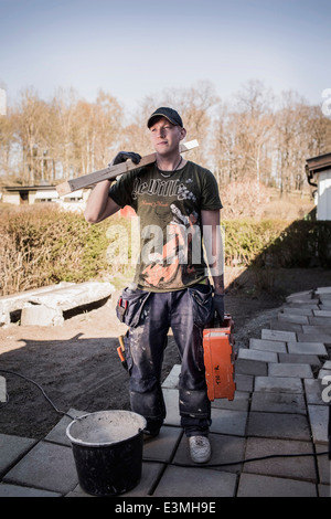 Male carpenter with wooden plank and toolbox standing at site - Stock Photo