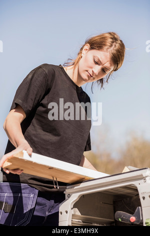 Low angle view of female carpenter working outdoors - Stock Photo
