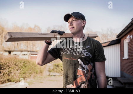 Male carpenter carrying wooden plank at construction site - Stock Photo