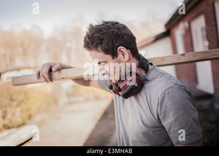 Carpenter carrying wooden plank at construction site - Stock Photo