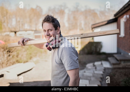 Side view portrait of smiling carpenter carrying wooden plank at construction site - Stock Photo