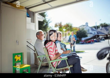 Portrait of mother and daughter smiling in garage - Stock Photo