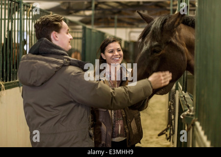Happy young couple stroking horse in stable - Stock Photo