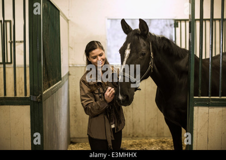 Smiling young woman with horse in stable - Stock Photo