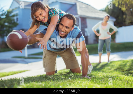 Father and daughter playing football in yard - Stock Photo