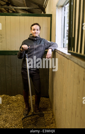 Full length portrait of confident young man with pitchfork in horse stable - Stock Photo