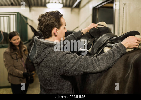 Young man preparing horse in stable with woman in background - Stock Photo