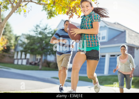 Family playing football in sunny street - Stock Photo