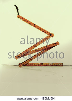 Businessman standing high up at the edge of folding ruler - Stock Photo