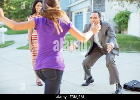Daughter running to father in driveway - Stock Photo