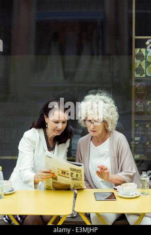 Senior women reading newspaper at outdoor cafe - Stock Photo