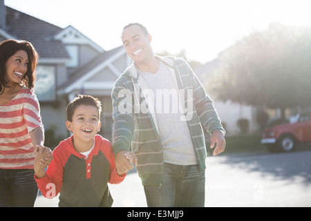 Happy family running on sunny street - Stock Photo