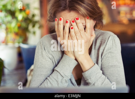 Sad young woman sitting with head in hands at home - Stock Photo