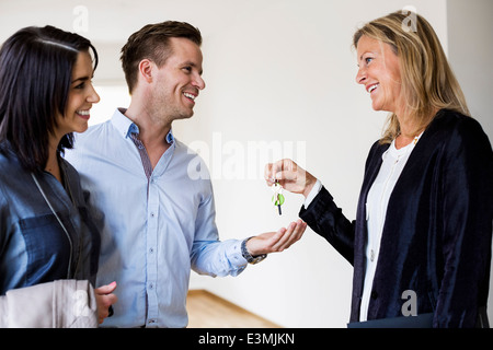 Happy real estate agent giving keys to couple in new house - Stock Photo