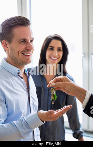 Cropped image of real estate agent handing over keys to couple in new house - Stock Photo