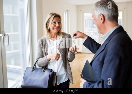 Happy male real estate agent giving keys to woman in new house - Stock Photo