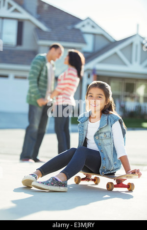 Portrait of smiling girl on skateboard in driveway - Stock Photo