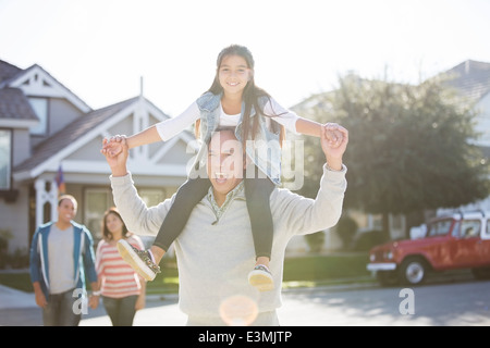 Portrait of grandfather carrying granddaughter on shoulders - Stock Photo