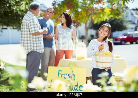 Portrait of smiling girl holding lemons at lemonade stand - Stock Photo