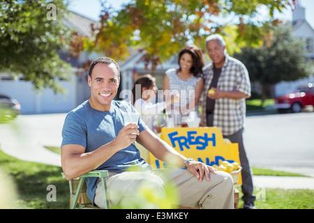 Portrait of smiling man drinking lemonade at lemonade stand - Stock Photo