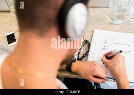 Rear view of young businessman writing in book at office desk - Stock Photo