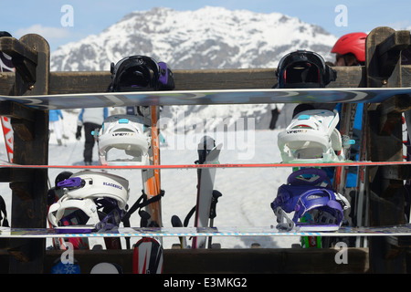 Snowboards, helmets, skis left by people taking a break from the snow on the mountains in Italy - Stock Photo