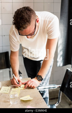 Young businessman writing adhesive notes on desk at new office - Stock Photo