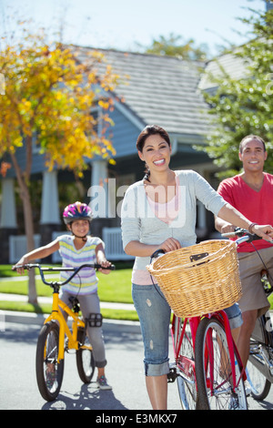 Portrait of happy family with bicycles in street - Stock Photo