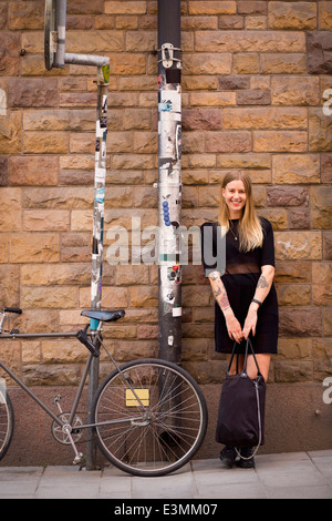 Full length portrait of happy young woman with purse standing on sidewalk against stone wall - Stock Photo