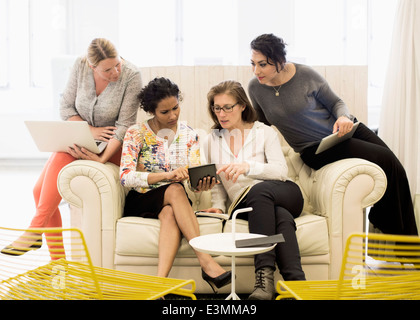 Creative businesswomen using digital tablet together on sofa in office - Stock Photo