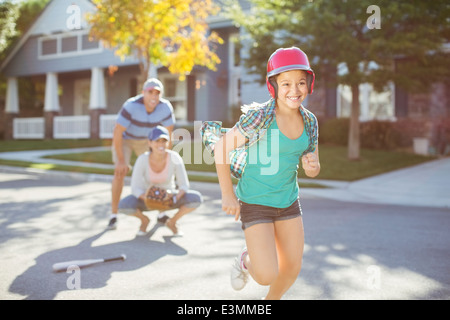 Family playing baseball in street - Stock Photo