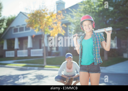 Portrait of mother and daughter playing baseball in street - Stock Photo