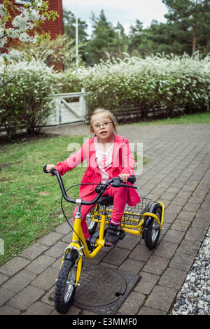 Portrait of girl with down syndrome riding bicycle in lawn - Stock Photo