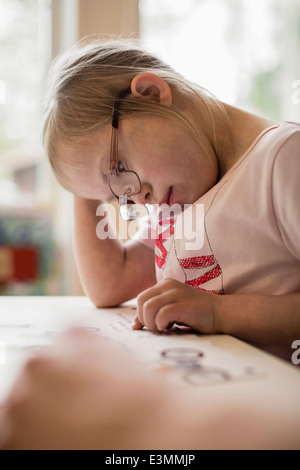 Girl with down syndrome studying at table - Stock Photo