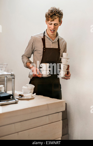 Waiter carrying stack of coffee cups in cafe - Stock Photo