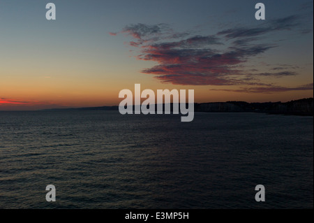 Clouds over cliffs and sea, sunrise - Stock Photo
