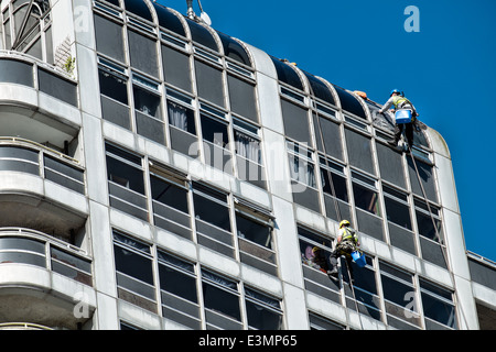 Window cleaners cleaning windows on the David Murry John building and Brunel shopping Center logo, Swindon, Wiltshire, - Stock Photo