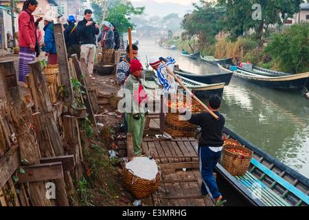 Farmers unload tomatoes, Nyaung Shwe, Inle Lake, Myanmar, Asia - Stock Photo