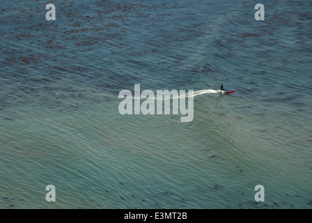 Lone surfer rides a gentle summer swell on a longboard at Bluff Cove in Palos Verdes near Los Angeles, California, - Stock Photo