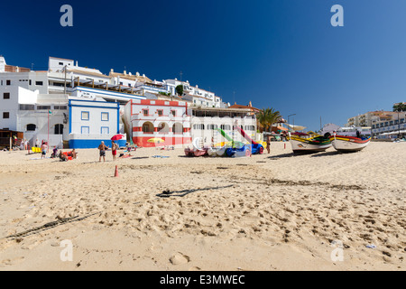 Holidaymakers on the sandy beach at the small coastal town of Carvoeiro in the Algarve - Stock Photo