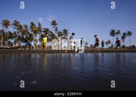 Banda Aceh, Aceh, Indonesia. 25th June, 2014. Teenagers playing football at a beach in Banda Aceh, Aceh, Indonesia.Football - Stock Photo
